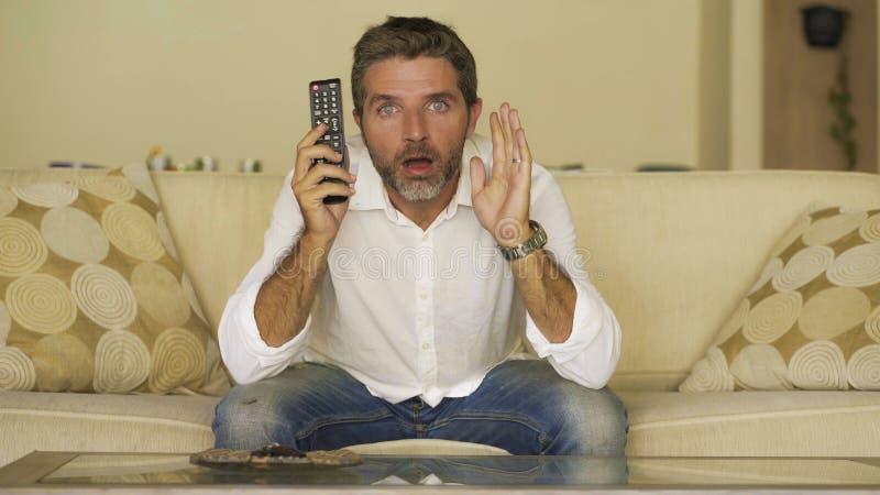 Junge attraktive überraschte und entsetzte aufpassende Fernsehnachrichten des Mannes oder überraschender Film auf der Wohnzimmers stockbild