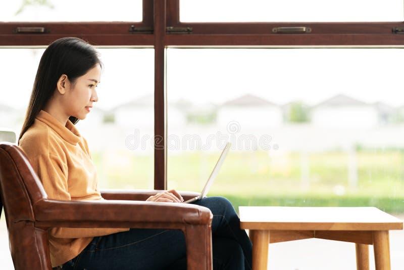 Junge attraktive asiatische Frau, die an der Cafékaffeestube denkt und schreibt Bloginformationen durch die Anwendung oder das Sc stockbild