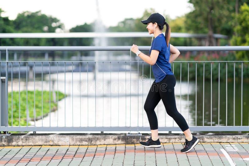 Junge attraktive asiatische Läuferfrau, die öffentlich am Natur-Stadtpark der Bürgersteigsweise mit dem Seewasser-Ansichttragen b stockfoto