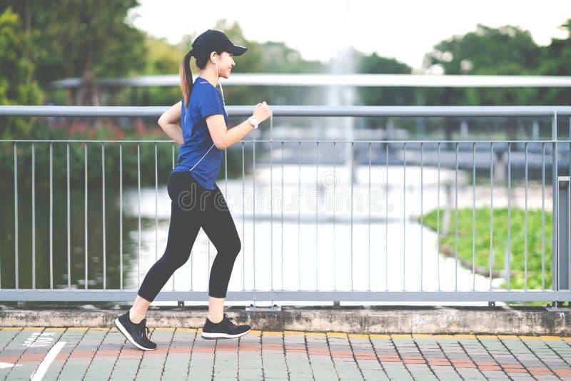 Junge attraktive asiatische Läuferfrau, die öffentlich am Natur-Stadtpark der Bürgersteigsweise mit Seewasser läuft lizenzfreie stockfotografie