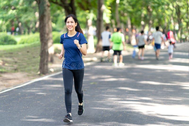 Junge attraktive asiatische Läuferfrau, die in städtischen allgemeinen Naturpark in der Stadt trägt blaue oder schwarze sportlich stockfoto
