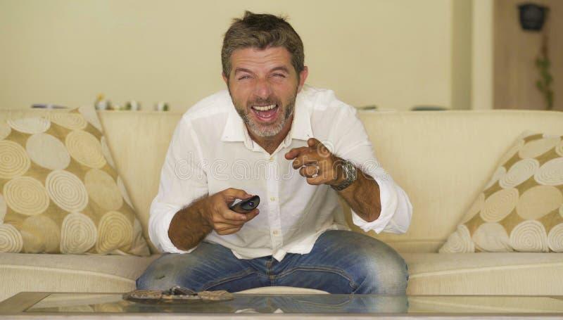 Junge attraktive aufpassende lustige Show des glücklichen und netten Mannes Fernsehoder Fernsehfernsitzen entspannte Holding des  stockfotografie
