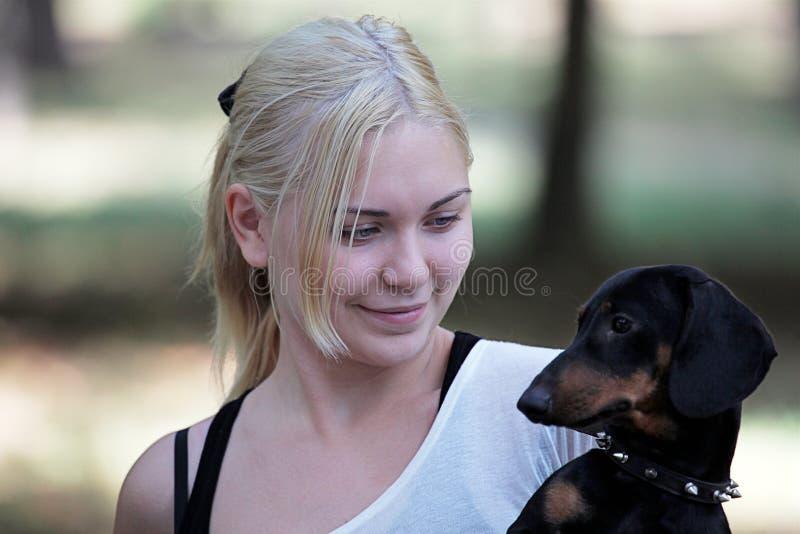 Junge attraktive blonde lächelnde Frau mit einem Dachshund auf ihrer Hand Sie schaut zum Hund lizenzfreies stockfoto