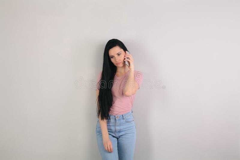 Junge attraktive brunette Frau mit dem langen Haar, welches die tragenden Blue Jeans und rosa das Hemd des grauen Hintergrundes b stockfotos