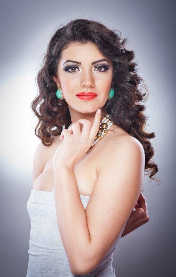Junge attraktive Brunettedame mit dem Make-up und schöner Frisur, die auf grauem Hintergrund im Studio aufwerfen stockfoto