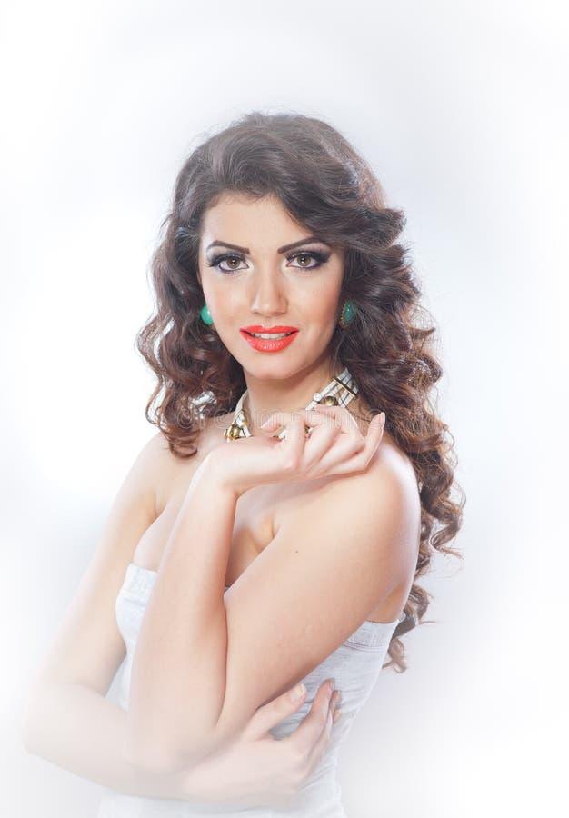 Junge attraktive Brunettedame mit dem Make-up und schöner Frisur, die auf grauem Hintergrund im Studio aufwerfen lizenzfreie stockbilder