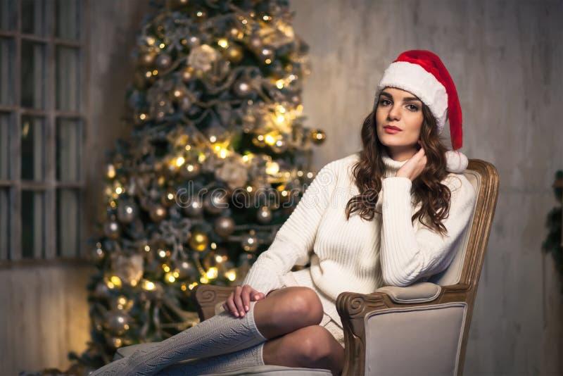 Junge attraktive Brunettefrau in Sankt-Hut nahe Weihnachtsbaum stockfotografie