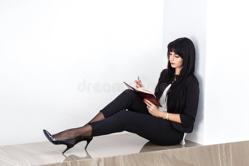 Junge attraktive ernste brunette Frau gekleidet in einem schwarzen Anzug, der auf einem Boden in einem Büro, lesend in einem Noti stockfotos