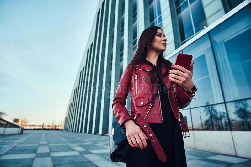 Junge attraktive Frau in der roten Jacke genie?t drau?en gehen bei der Aufwartung jemand mit Handy in den H?nden stockfotografie