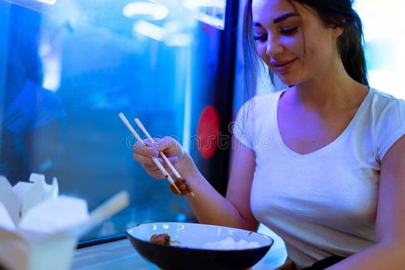 Junge attraktive Frau, die asiatische Nahrung mit Essst?bchen am Caf? oder am Restaurant isst lizenzfreie stockfotos