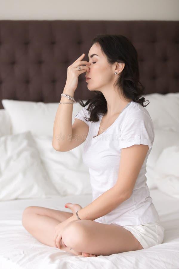 Junge attraktive Frau, die an Atmungshaltung des abwechselnden Nasenloches tut stockbild