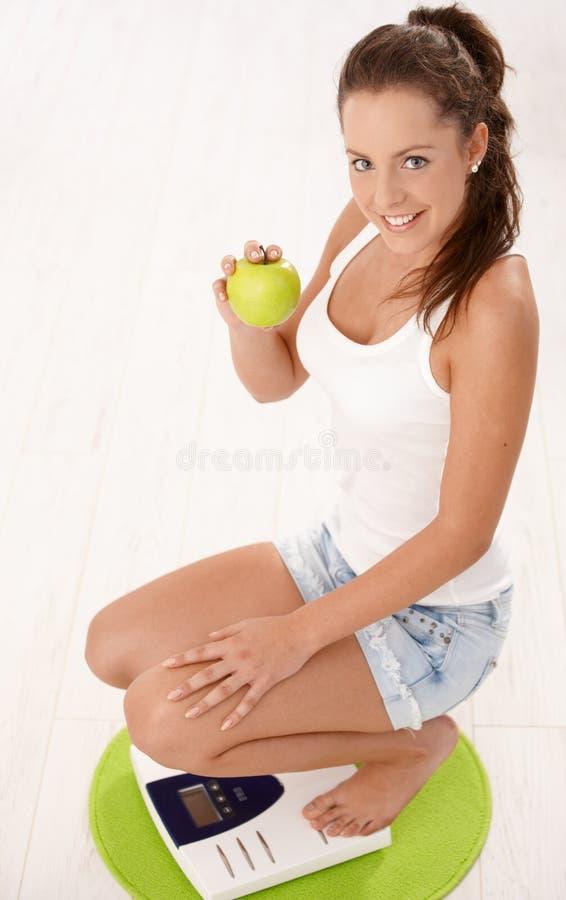 Junge attraktive Frau, die auf dem Skalalächeln hockt lizenzfreies stockbild
