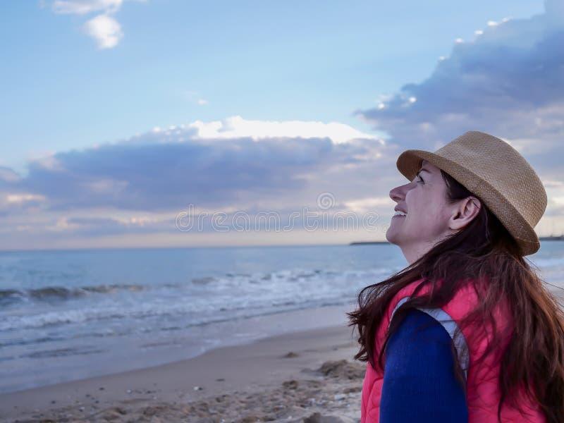Junge attraktive Frau, die auf dem Strand lächelt sitzt, den Himmel, copyspace betrachtend stockfoto