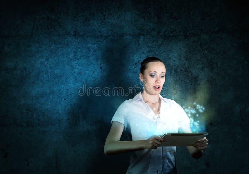 Junge attraktive Frau, die eine Tablette hält lizenzfreies stockfoto