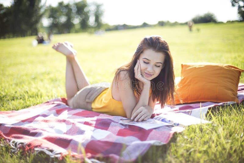 Junge attraktive Frau, die eine Zeitschrift liest lizenzfreie stockfotografie