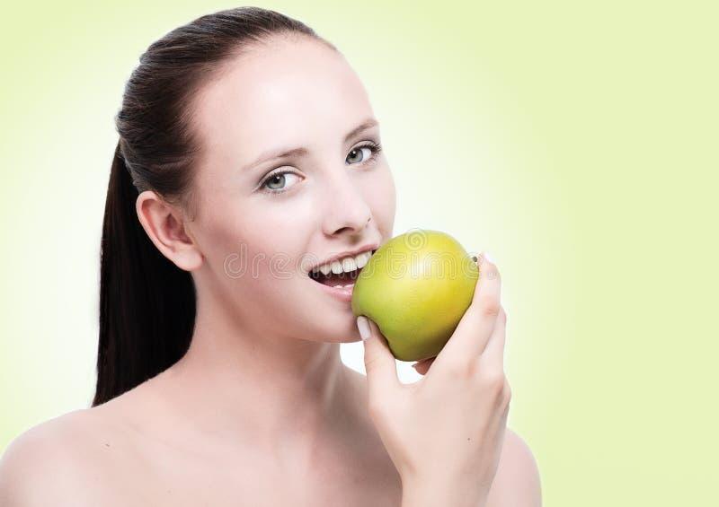 Junge attraktive Frau, die einen Apfel isst stockfotografie