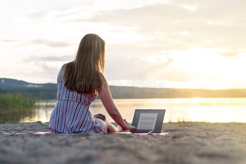 Junge attraktive Frau, die Laptop auf Strand bei Sonnenuntergang verwendet lizenzfreies stockfoto