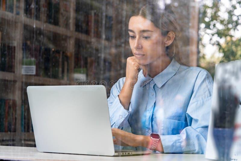 Junge attraktive Frau, die an Laptop in der modernen Bibliothek arbeitet lizenzfreie stockbilder