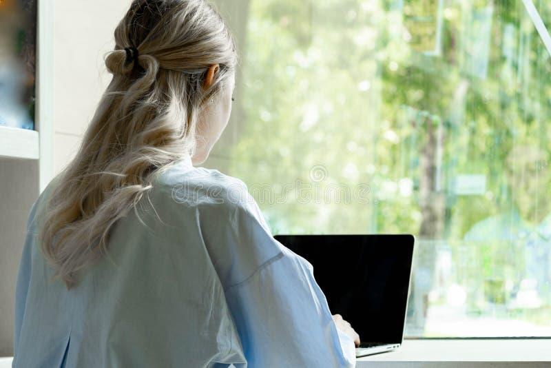 Junge attraktive Frau, die an Laptop in der modernen Bibliothek arbeitet stockfotos