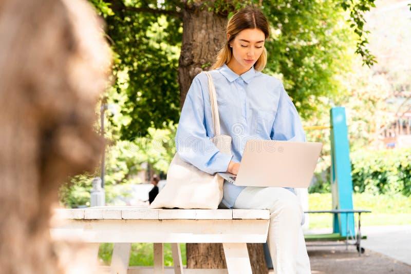 Junge attraktive Frau, die an Laptop am modernen Park arbeitet stockbild