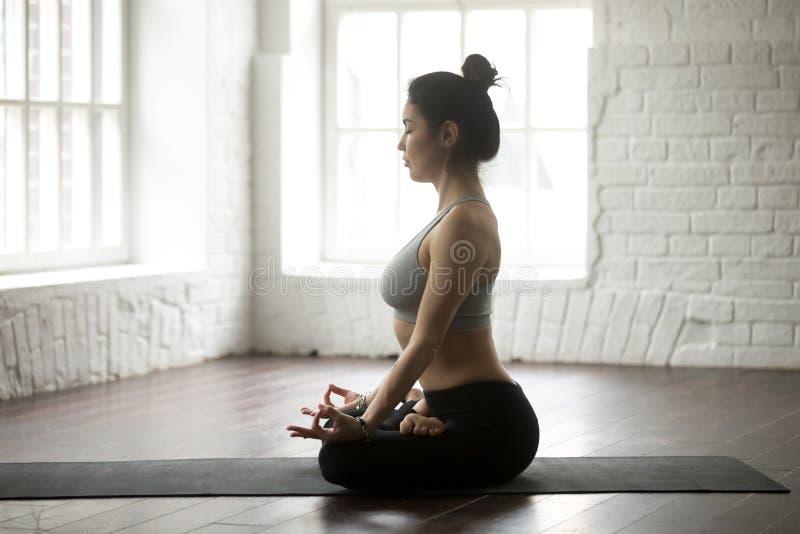 Junge attraktive Frau, die in Lotus-Haltung, weißes Dachbodenstudio sitzt lizenzfreies stockfoto