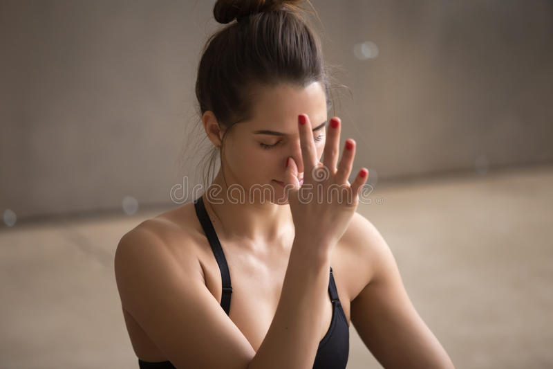 Junge attraktive Frau, die nadi shodhana pranayama, grauen Bolzen macht lizenzfreie stockfotos
