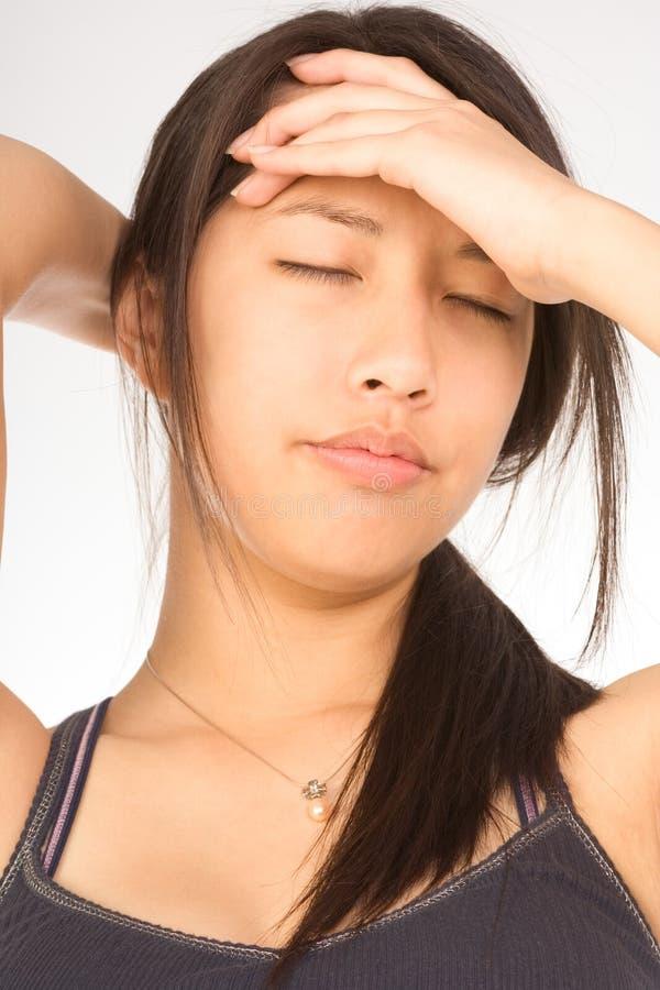 Junge attraktive Frau, die unter Kopfschmerzen leidet lizenzfreie stockbilder