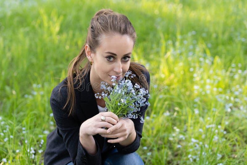 Junge attraktive Frau holte einen Blumenstrauß von Vergissmeinnichten zu ihrem Gesicht stockfotografie