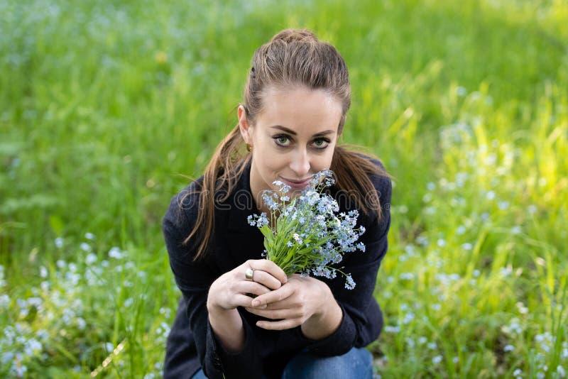 Junge attraktive Frau holte einen Blumenstrauß von Vergissmeinnichten zu ihrem Gesicht lizenzfreie stockfotografie