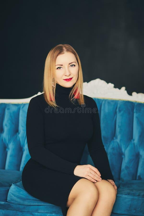 Junge attraktive Frau im schwarzen Kleid ist, lächelnd zuhause sitzend und auf blauem Sofa Schöne Dame in einem dunklen Kleid auf lizenzfreie stockfotos