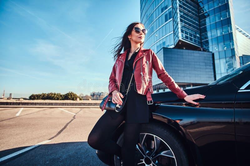 Junge attraktive Frau k?hlt am hellen sonnigen Tag nahe bei ihrem Auto lizenzfreie stockbilder