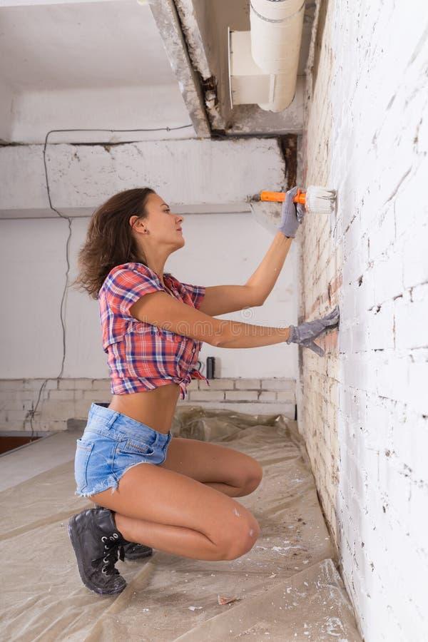 Junge attraktive Frau malt weiße Backsteinmauer und Pinsel lizenzfreie stockfotografie