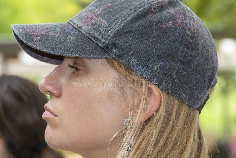 Junge attraktive Frau mit dem blonden Haar und einer abgenutzten Kappe auf ihrer kopf- Seitenansicht mit einem geringfügigen Sche stockfotografie