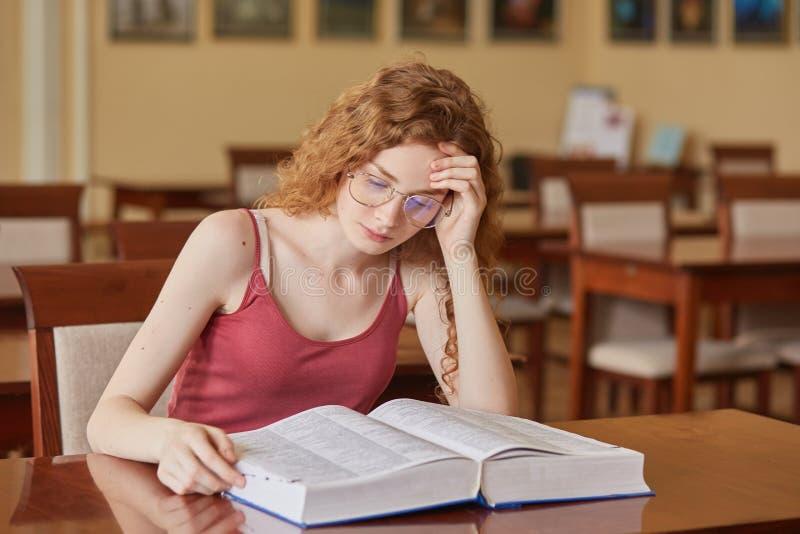 Junge attraktive Frau mit dem gewellten foxy Haar, das am Schreibtisch in der Universitätsbibliothek, junger kaukasischer Student lizenzfreie stockbilder