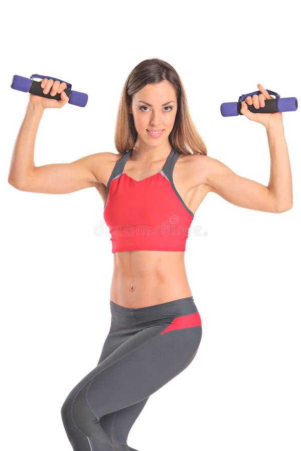 Junge attraktive Frau mit Gewichten lizenzfreies stockfoto