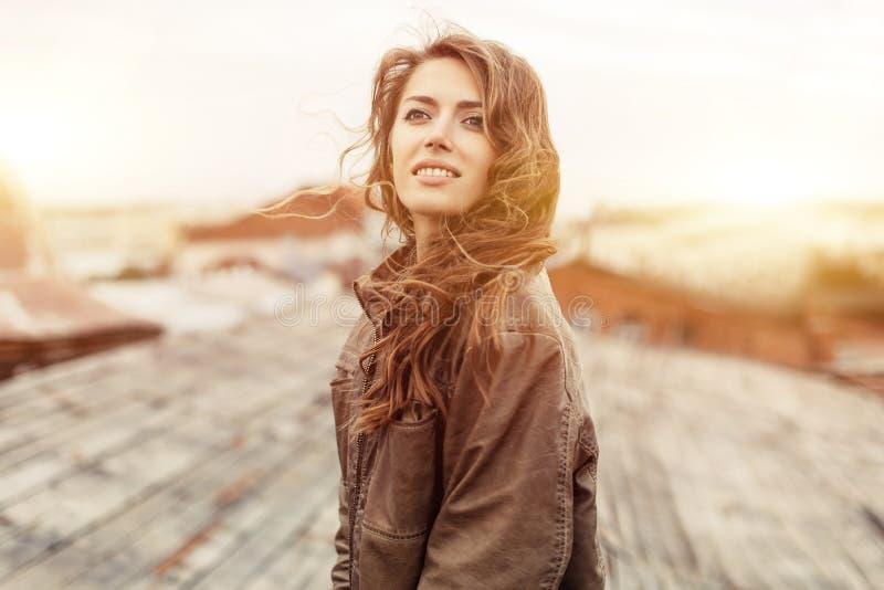 Junge attraktive Frau mit guter Laune schöne Stadtlandschaft bei der Stellung genießend auf einem Dach des Gebäudes, bezaubernde  stockbild
