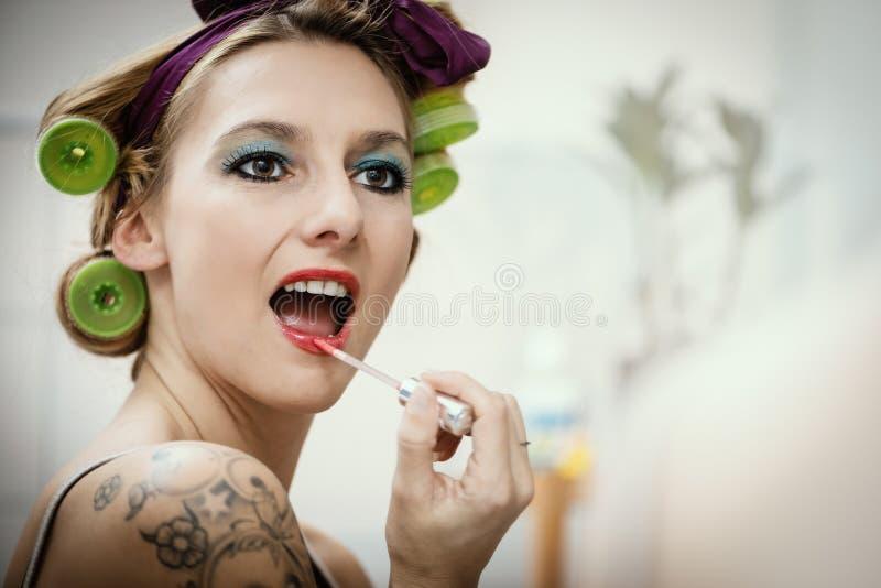 Junge attraktive Frau mit Haarrolle stockbild