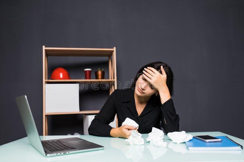 Junge attraktive Frau am modernen Schreibtisch, arbeitend an dem Laptop und massieren Tempel, um über konstante Kopfschmerzen zu  stockfotografie