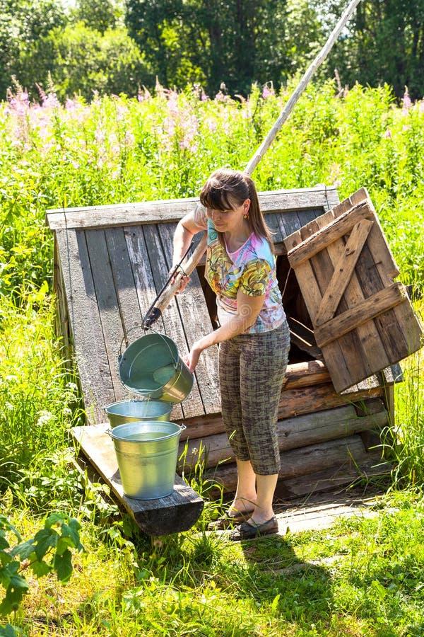 Junge attraktive Frau nahe dem hölzernen Wasserbrunnen des Dorfs stockfotografie