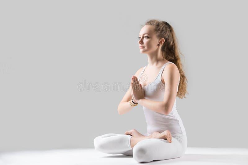 Junge attraktive Frau in Padmasana-Haltung mit namaste, grauer Bolzen stockbilder