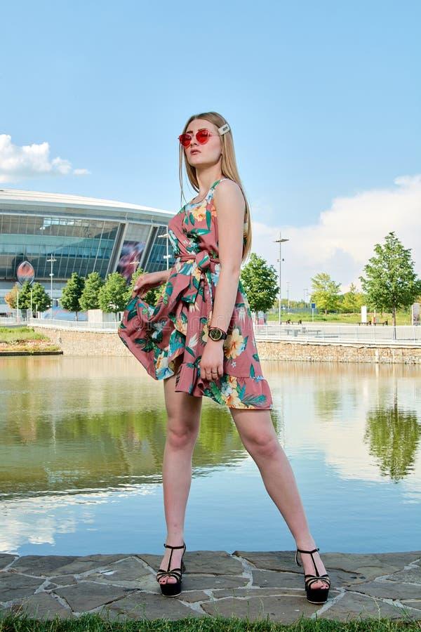 Junge attraktive Frau Rote Sonnenbrille, Farbkleid M?dchen ` s Portr?t Fu?ballstadionshintergrund stockbild