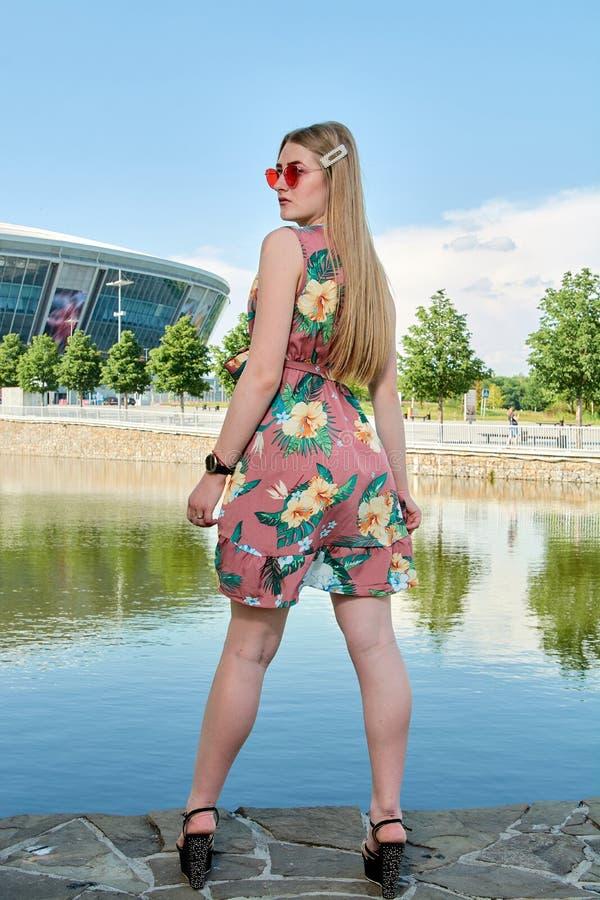 Junge attraktive Frau Rote Sonnenbrille, Farbkleid M?dchen ` s Portr?t Fu?ballstadionshintergrund lizenzfreies stockfoto