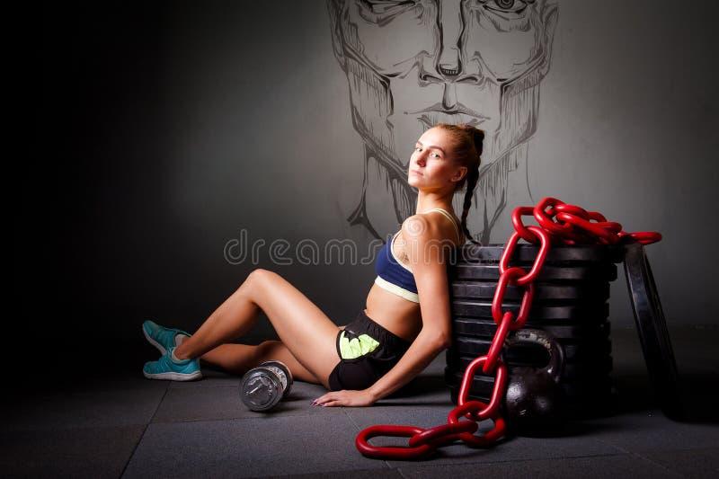 Junge attraktive Frau sitzen auf der Flor mit Sportausrüstung lizenzfreie stockbilder