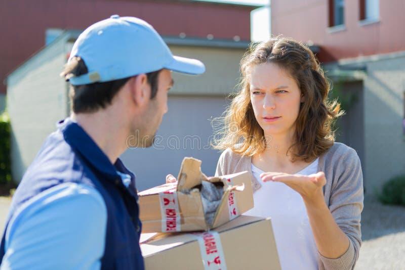 Junge attraktive Frau verärgert gegen Lieferer stockfotos