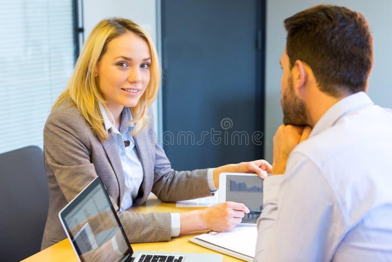 Junge attraktive Frau während des Vorstellungsgesprächs unter Verwendung der Tablette lizenzfreies stockbild
