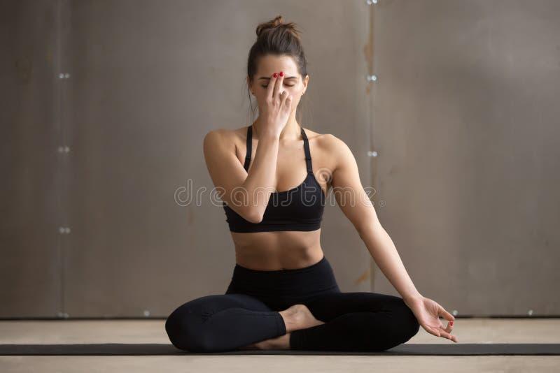 Junge attraktive Frau, welche die abwechselnde Nasenloch-Atmung, grau macht lizenzfreies stockfoto