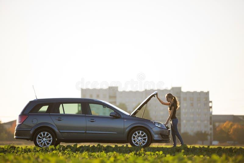 Junge attraktive Frauenstellung am silbernen Auto, das unter geknallter Haube auf klarem Himmelkopien-Raumhintergrund schaut Tran stockbild