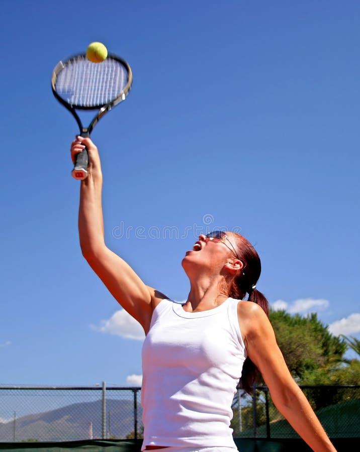 Junge attraktive gebräunte gesunde Frau, die Tennis in der Mittagssonne mit blauem Himmel spielt lizenzfreie stockfotografie