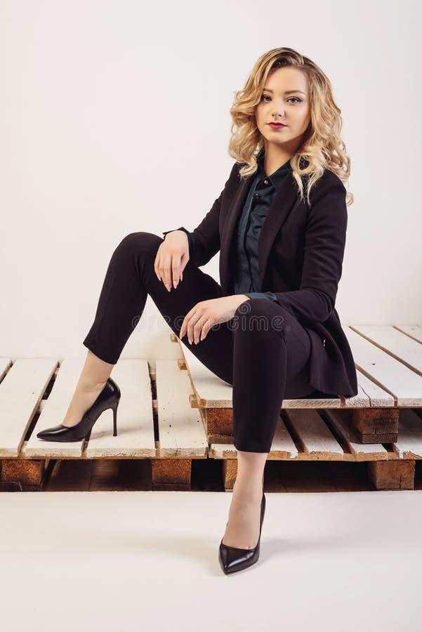 Junge attraktive Geschäftsfrau in der teuren Klage und in den Schuhen sitzt auf gemalten Paletten stockfotos