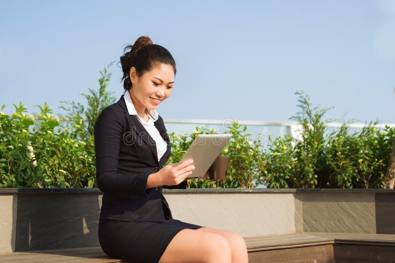 Junge attraktive Geschäftsfrau des Porträts, die mit digitalem Vorsprung arbeitet stockbild